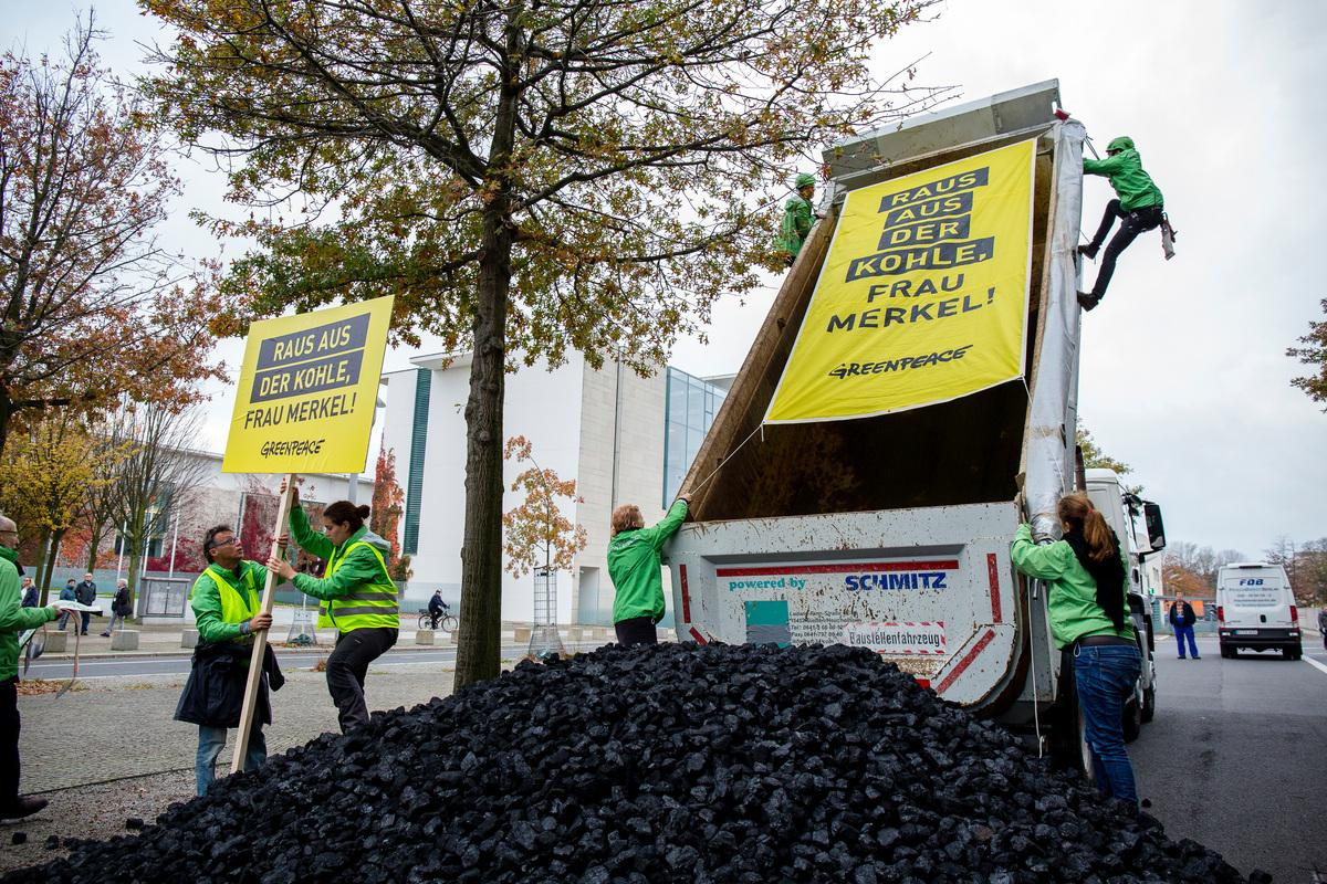 """Exit coal, Ms Merkel"" - Greenpeace activists unload a truckload of coal in front of the German chancellery ahead of the coalition talks - (c) Jan Zappner/Greenpeace"