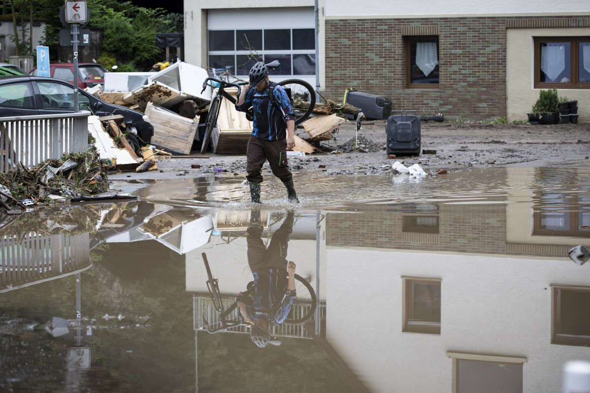 Photo shows man with bicycle over shoulder wading through flooding in city of Altena in Germany 2021. Photo: Land NRW / Ralph Sondermann.