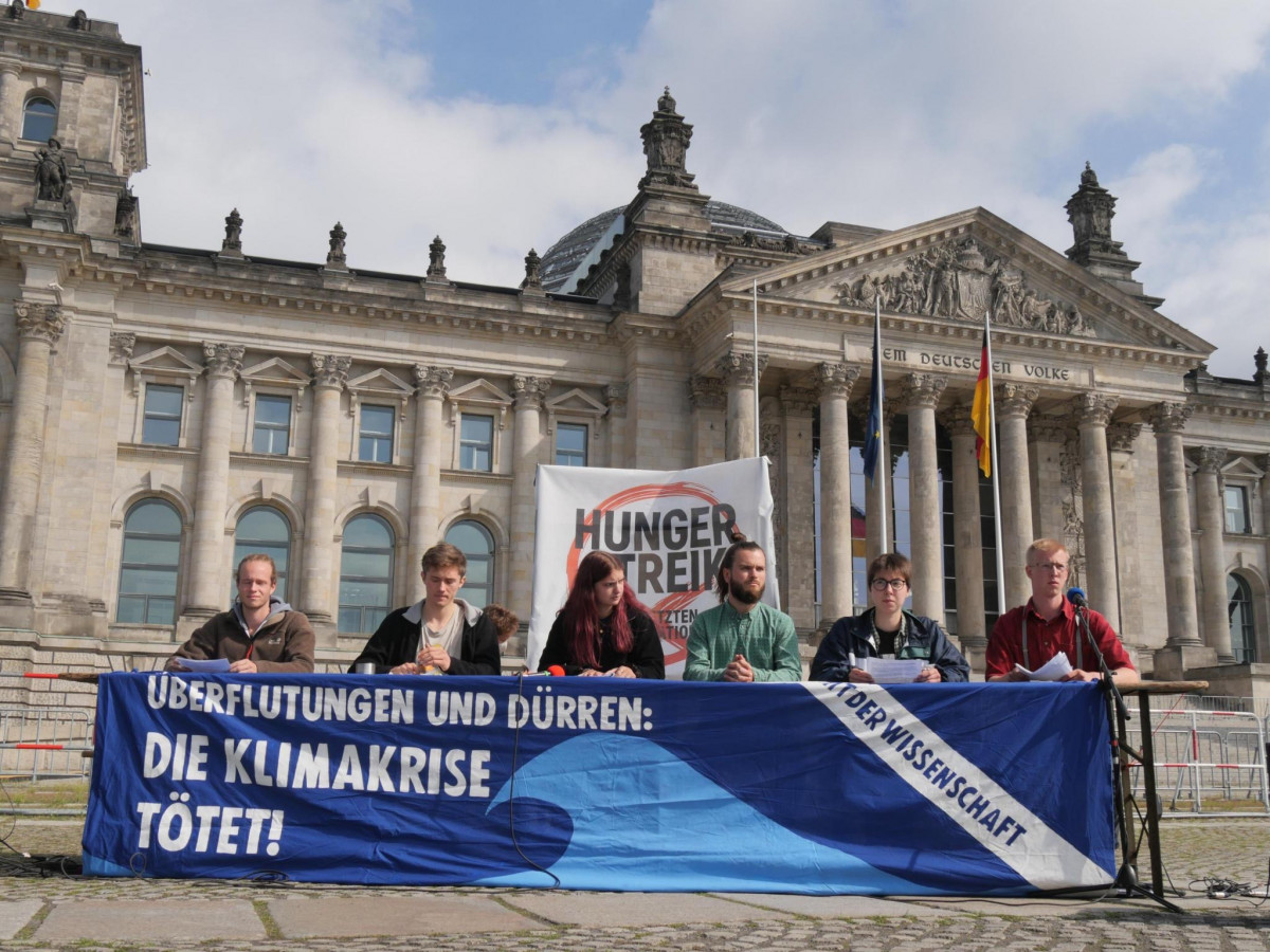 The six hunger strikers giving a press conference in front of Germany's federal parliament building in Berlin. Photo: Hungerstreik2021.