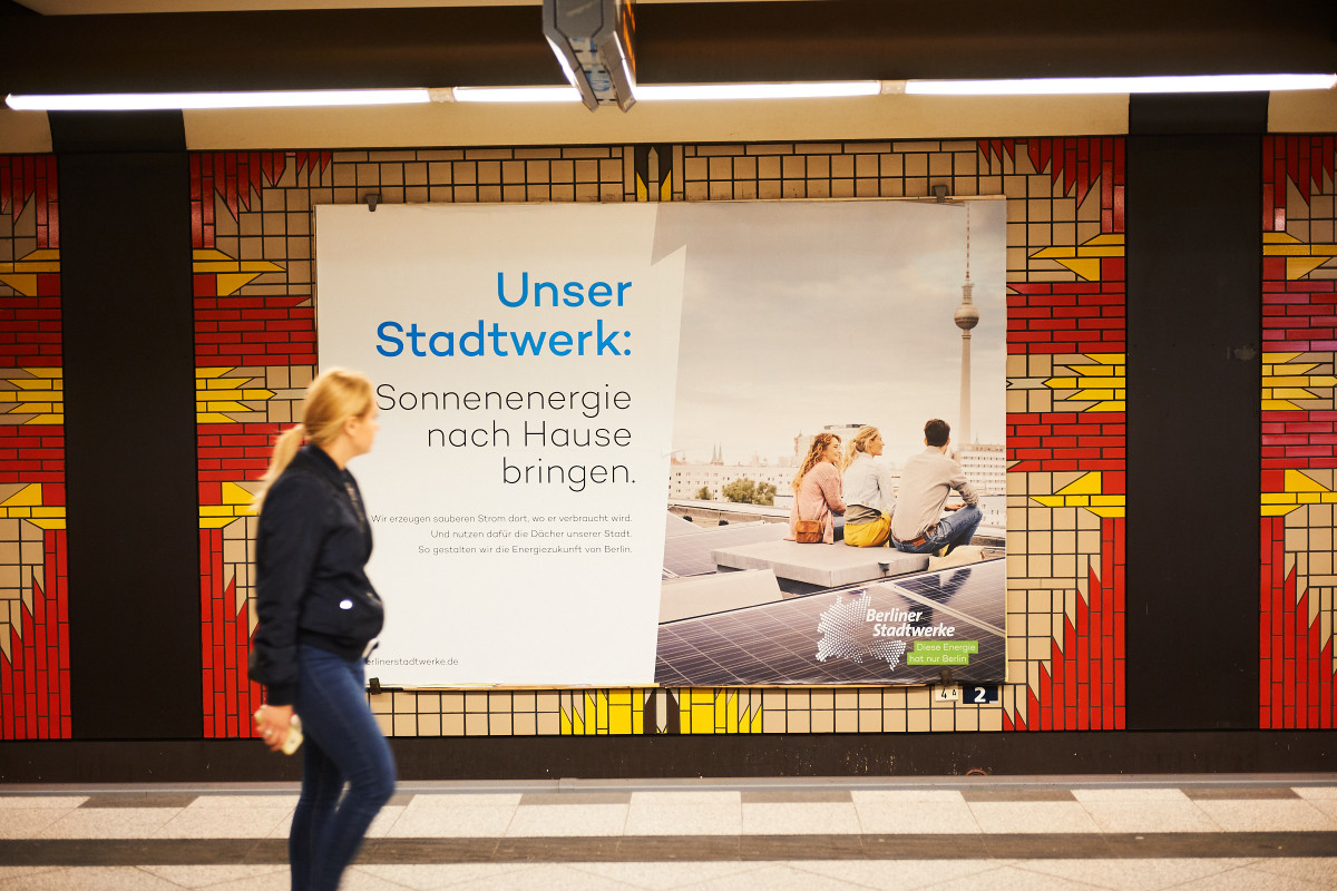 Photo shows a billboard advertising local power production by Berliner Stadtwerke in a Berlin subway station. Photo: Darius Ramazani.
