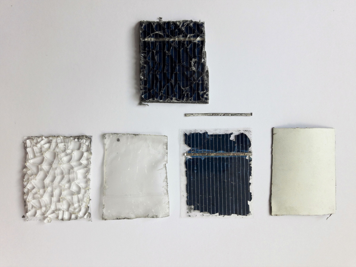 Photo shows recycled materials from solar PV module: cover glass, EVA-foil, silicon wafer, bus bar and back-foil. Photo: FLAXRES GmbH.