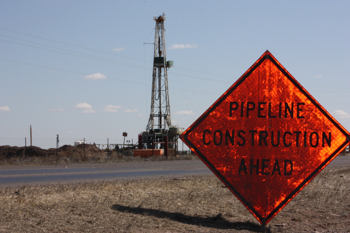 """Photo shows oil and gas drilling site in Verhalen, Texas, in the Permian Basin, and a sign that reads """"pipeline construction ahead"""". Photo: CLEW/Wettengel 2020."""